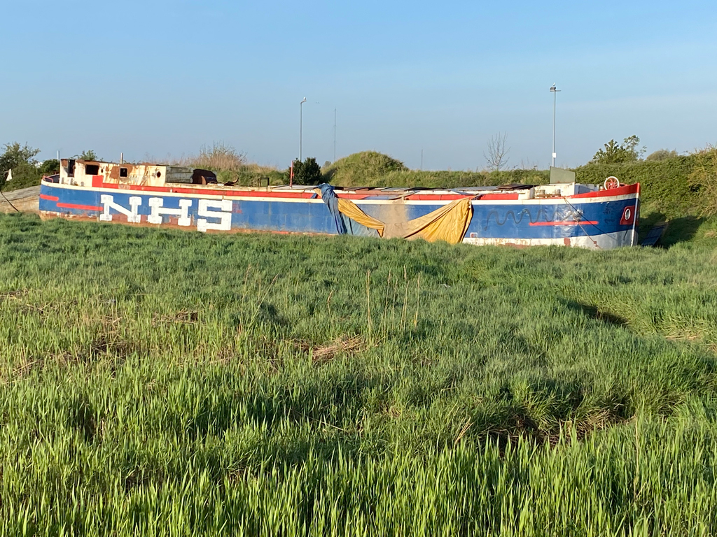 The Tosca, an abandoned ship in Boal Quay, King's Lynn, with NHS graffitti